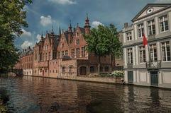 树木繁茂的庭院和砖瓦房在运河` s在一个晴天渐近在布鲁日 免版税库存图片