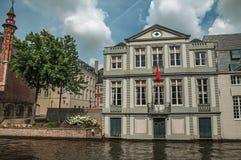 树木繁茂的庭院和砖瓦房在运河` s在一个晴天渐近在布鲁日 免版税图库摄影