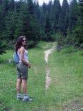 树木繁茂的线索的女性远足者 免版税库存图片