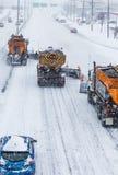 树清除高速公路的排队的除雪机 免版税库存图片