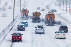 树清除高速公路的排队的除雪机 免版税图库摄影