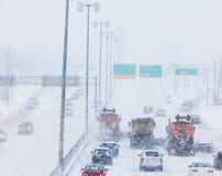树清除高速公路的排队的除雪机 免版税库存照片