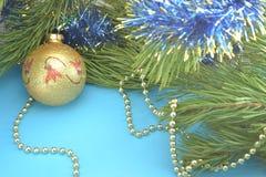 树玩具:金黄,黄色,球、圣诞节和新年在用金小珠装饰的杉木分支在蓝色背景 免版税库存照片