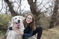 树的妇女享受与金毛猎犬的天 库存图片