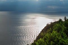 树的风景在山、海和多云天空的 库存照片