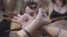 树精或森林神仙的手有被绘的眼睛的在跳舞和盖面孔的棕榈和错误爪 古老仪式 股票视频