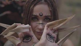 树精或森林神仙的手有被绘的眼睛的在跳舞和盖面孔的棕榈和错误爪 古老仪式 影视素材