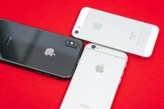 树苹果计算机在红色背景的iPhone ` s 免版税库存图片
