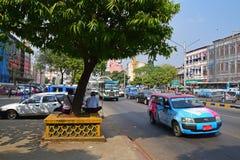 树荫在与车的一棵大树下在Sule塔路在仰光,缅甸 免版税库存照片