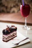 黑树莓蛋糕服务与黑莓果饮料 免版税库存照片