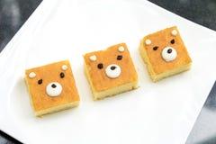 树逗人喜爱的熊面孔黄油在黑石头ta的白色盘结块 免版税库存图片