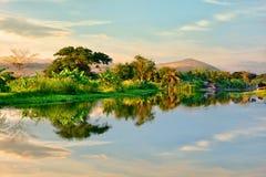树,山看法,平衡在水反映的天空 库存图片