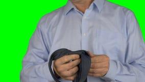 栓他的在照相机前面的一个成人白种人人的射击领带 人结领带 蓝色衬衣,射击的关闭 绿色屏幕 股票录像