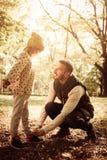 栓他的女儿鞋子的唯一父亲在公园 库存图片