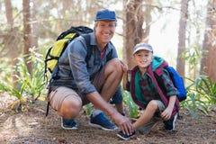 栓儿子的父亲画象鞋带在森林里 库存图片