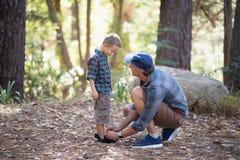 栓儿子的鞋带父亲在森林里 免版税图库摄影