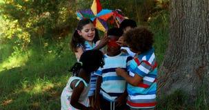 栓在他们的朋友的小组孩子眼罩在公园注视 股票录像