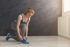 栓在体育的鞋带的妇女穿上鞋子特写镜头 库存照片