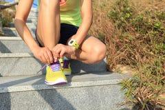 栓在石足迹的妇女赛跑者鞋带 库存图片