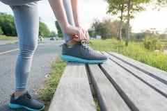 栓在跑鞋的运动的妇女鞋带在实践前 体育活跃生活方式概念 免版税库存照片