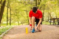 栓在轨道的英俊的年轻赛跑者鞋带在春天公园 在他附近是橙色热电偶 库存图片