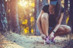 栓在运动鞋的妇女赛跑者鞋带 免版税图库摄影