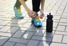 栓在运动鞋的少妇鞋带在摊铺机 站立在一个瓶水旁边 户外执行 免版税库存图片