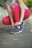 栓在运动鞋的特写镜头运动的女孩鞋带户外 图库摄影