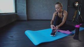栓在运动鞋的年轻运动员鞋带,夫人坐瑜伽的一个地毯 股票视频