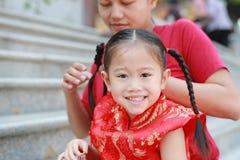栓她的女儿的头发的母亲画象 两根被栓的马尾辫头发 看照相机的儿童女孩 库存照片