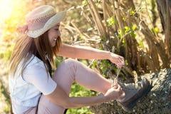 栓她的起动的美丽的年轻远足者在森林 免版税库存图片