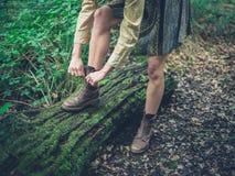栓她的鞋子的妇女在森林里 免版税库存照片