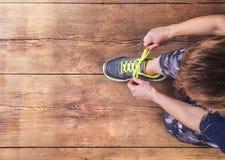 栓她的鞋子的年轻赛跑者 免版税库存照片