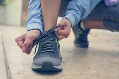 栓她的鞋带的女运动员在训练前 关闭 免版税库存图片