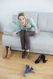 栓她的鞋带的快乐的偶然妇女坐长沙发 图库摄影