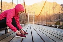 栓她的鞋带的适合和运动的妇女在奔跑前 免版税库存照片