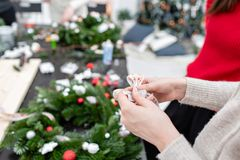 栓弓丝带的妇女,装饰圣诞节花圈 随员玩具和装饰与胶水枪 递特写镜头 重要资料 库存图片