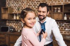 栓父亲的领带的女儿早晨和看的 免版税库存照片