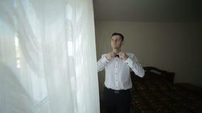 栓蝶形领结的白色衬衫的人在窗口附近 股票录像