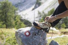 栓起动鞋带的女性远足者 免版税库存照片