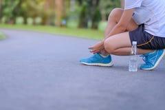 栓跑鞋的运动员妇女在室外的公园 免版税图库摄影