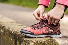栓运动的鞋子的女性手 免版税库存照片