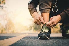 栓鞋带的人的特写镜头手在跑在健康的路期间 库存图片