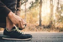 栓鞋带的人的特写镜头手在跑在健康的路期间 免版税库存图片