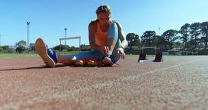 栓鞋带的女运动员在运动会比赛地点4k 股票录像