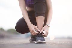 栓鞋带的少妇赛跑者在跑步的站立在fo前 库存图片