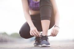 栓鞋带的少妇赛跑者在跑步的站立在fo前 免版税库存图片