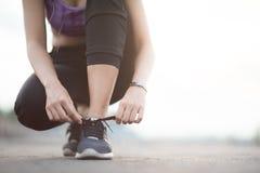 栓鞋带的少妇赛跑者在跑步的站立在fo前 免版税库存照片