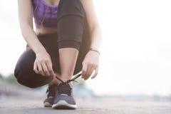 栓鞋带的少妇赛跑者在跑步的站立在fo前 免版税图库摄影