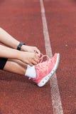 栓鞋带的少妇赛跑者 免版税库存图片